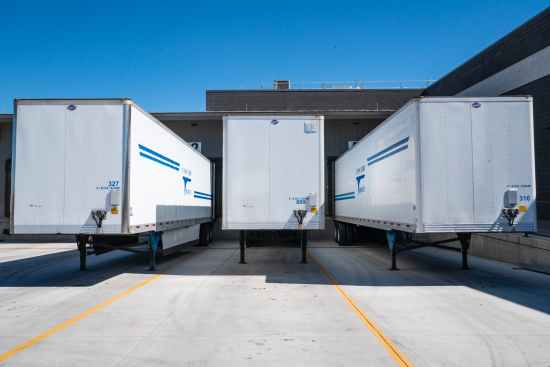 three white enclosed trailers