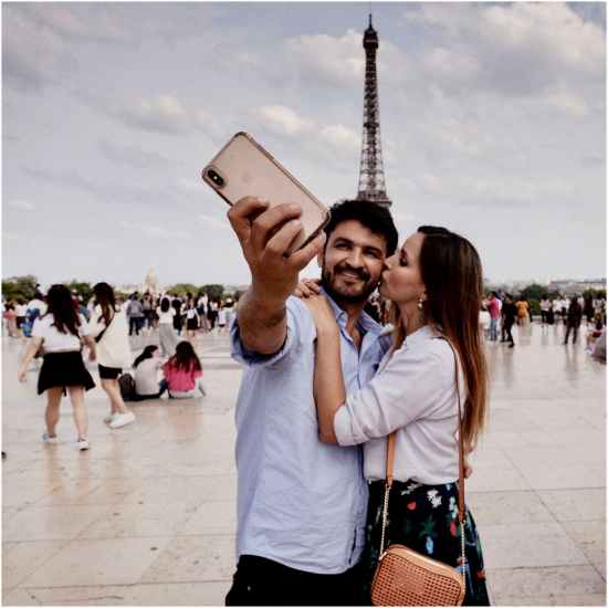 photo of hugging couple taking selfie with a crowd of people and the eiffel tower in the background