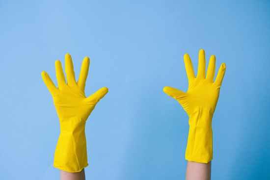 crop unrecognizable person in rubber gloves raising arms
