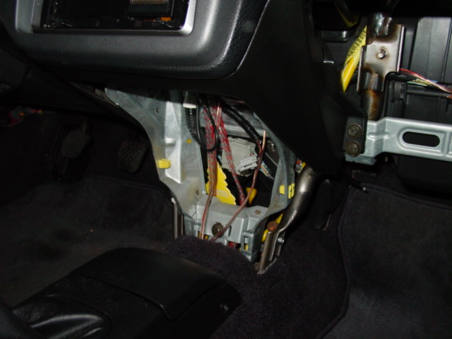 Remove the console below the radio. There are two screws under the radio and one on each side. There is also one harness plug that must be disconnected before you pull the console out.