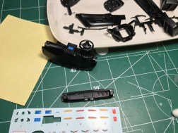 After painting the interior parts, I started assembly. The infotainment and steering wheel decals worked well. The flags for the seats disappeared on the black paint.