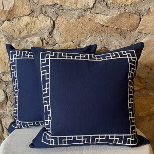 Navy pillow with white geometric greek key embroidery around the perimeter from Impressive Windows and Interiors in Hastings MN