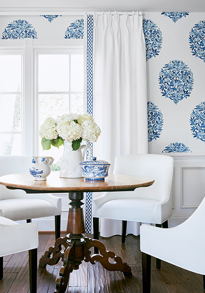 Dining room with white performance fabric upholstered custom chairs- white linen custom stationary drapery panels with lattice weave leading edge trim in navy blue- wallpaper with a white background and large scale navy blue floral medallion motif- Impressive Windows and Interiors Hastings MN