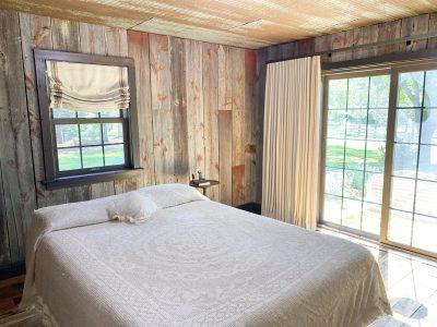 Restored farmhouse with custom roman shades with inset tape trim and custom ripplefold draperies over patio door