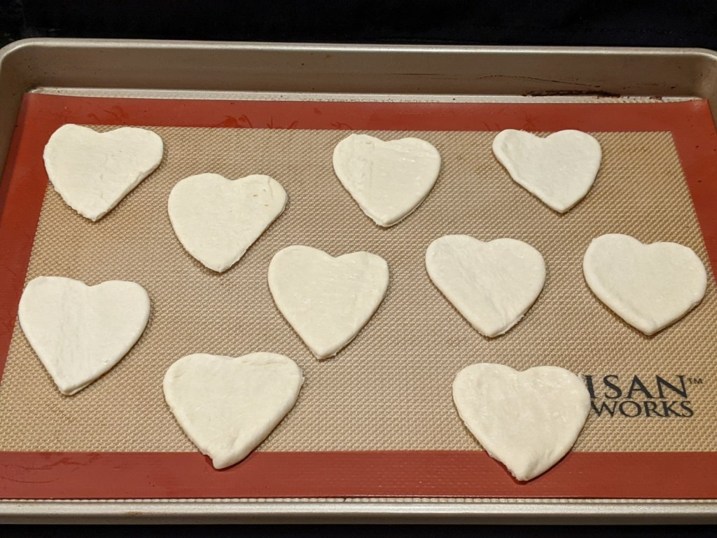 Place cut-out hearts on a silicone mat  on a baking pan