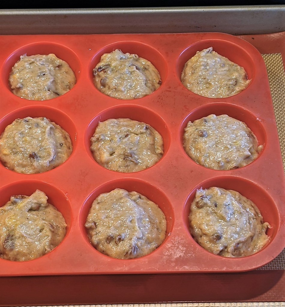 Muffin pan with batter on a baking sheet