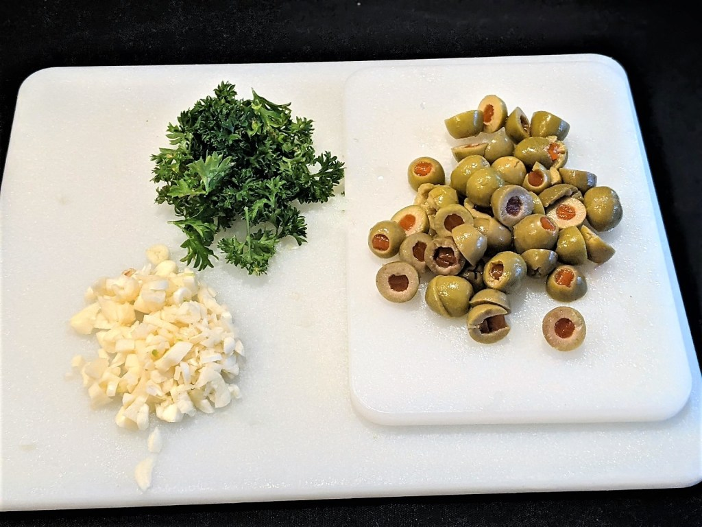 cutting board with garlic, parsley and sliced green olives
