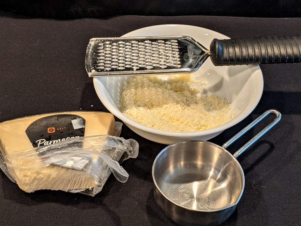 Parmesan cheese, bowl of cheese, grater and measuring cup