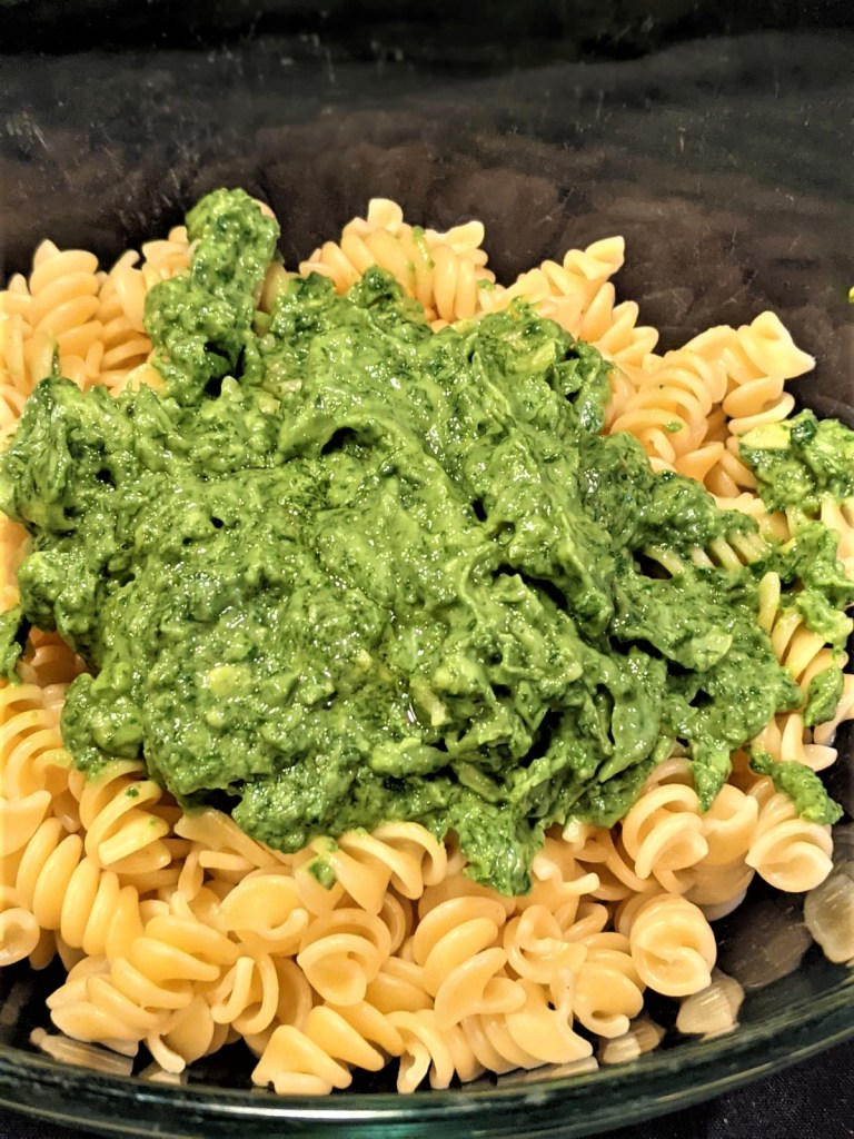 Pasta with green sauce on top of it