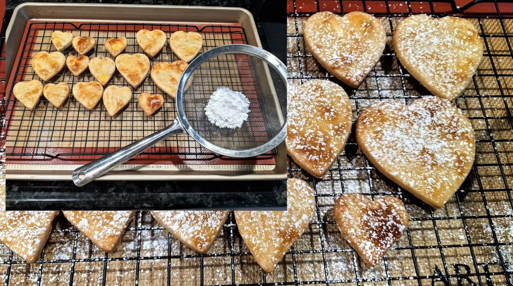 Cut-out hearts sprinkled with sugar on wire rack over baking pan.