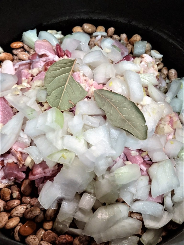 Image of onions, bacon and bay leaf added to the beans