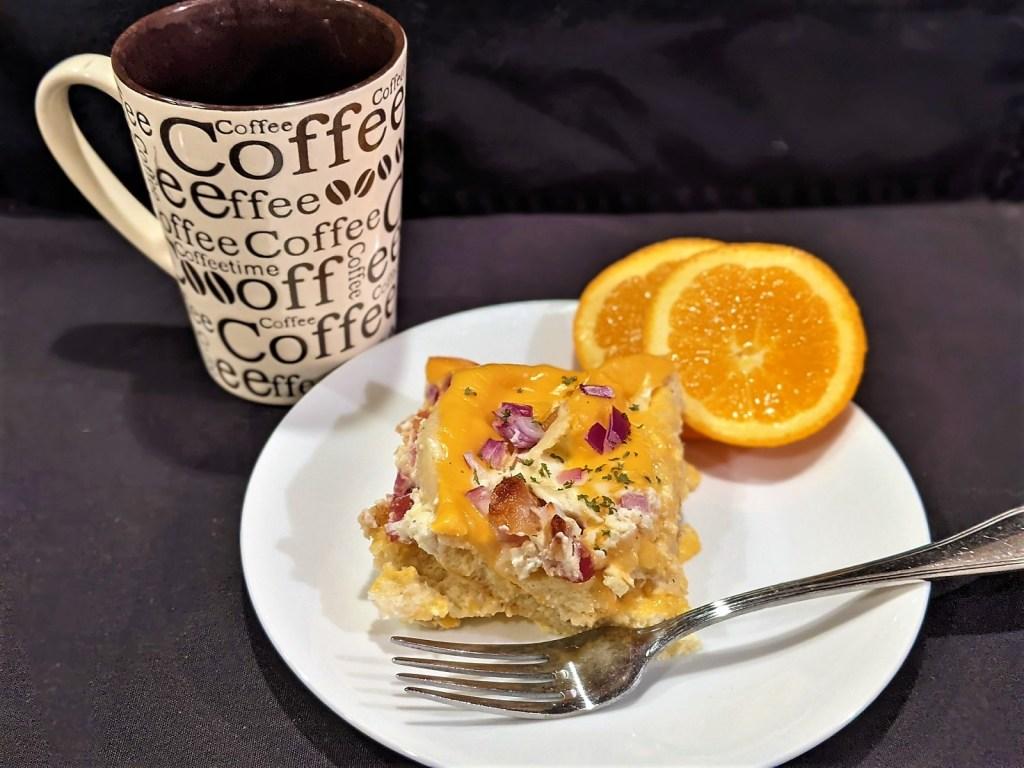 Coffee, casserole and orange on plate