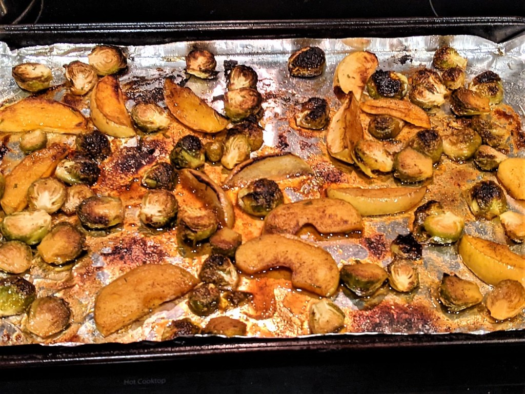 Sprouts and apple on baking sheet in broiler