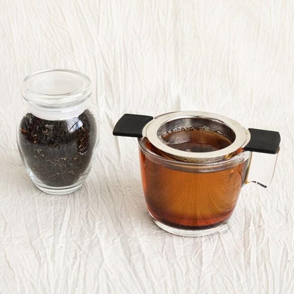 English breakfast tea leaves in a jar, english breakfast tea brewing in a glass