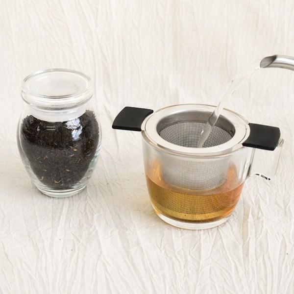 Mangalam black tea leaves in a jar, mangalam black tea brewing in a glass
