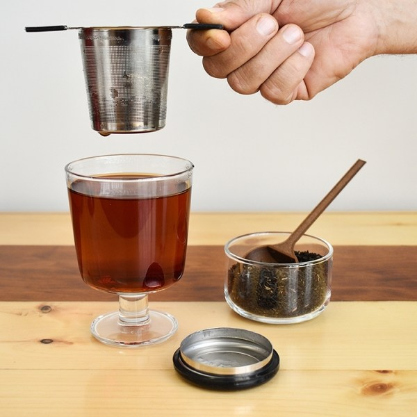 Tea infuser held over a glass filled with brewed tea