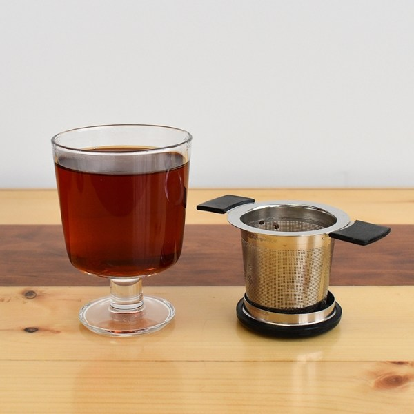 Tea infuser next to a glass of brewed tea