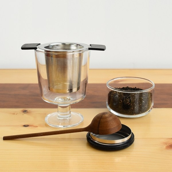 Tea infuser in an empty glass, loose tea leaves in a glass container and a tea scoop
