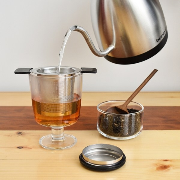 Pouring hot water over the tea infuser in an empty glass