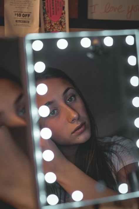 woman in front of vanity mirror
