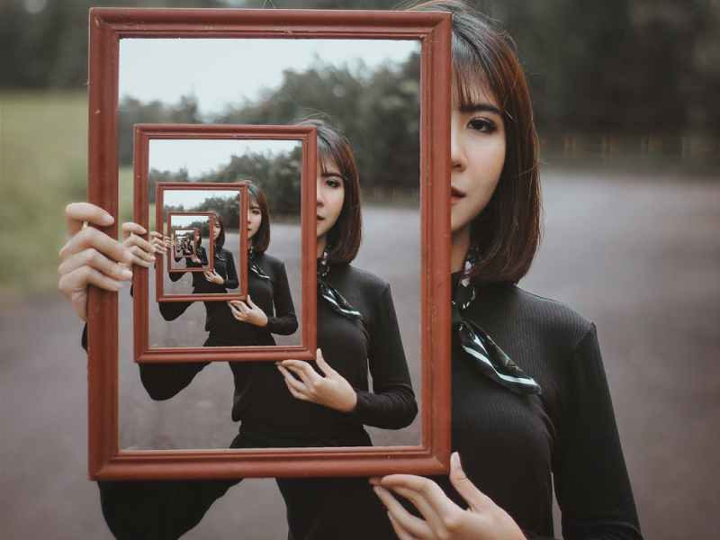 young woman with multiple reflection in mirror
