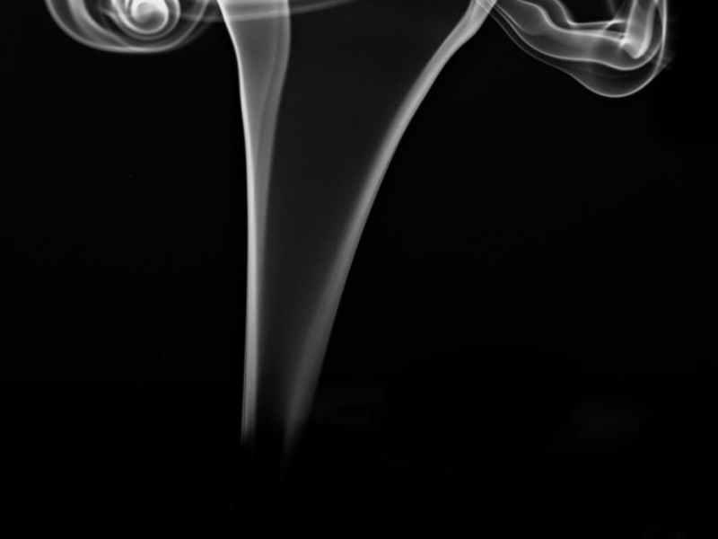 scent fume of burning incense stick against black background