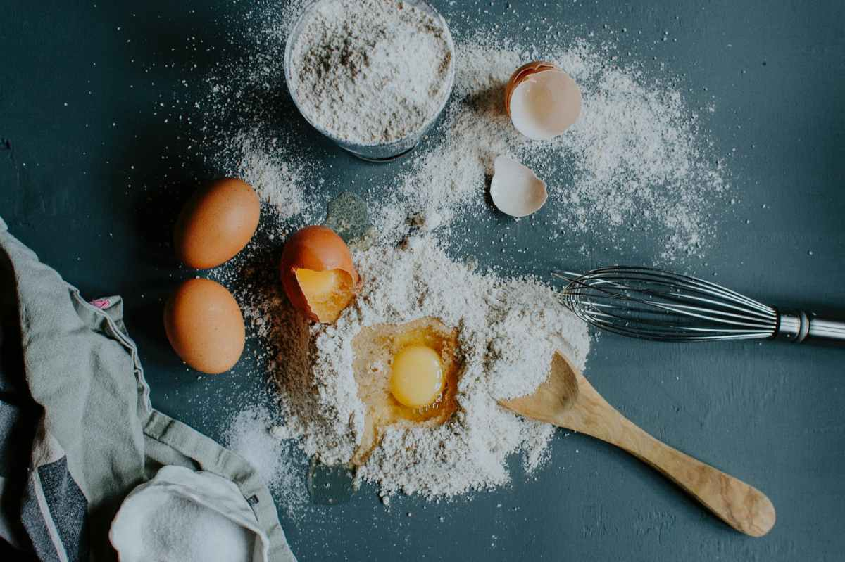 flour and broken eggs on table before dough kneading