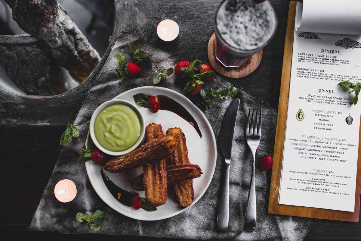 churro with avocado sauce and lavender dessert served on table