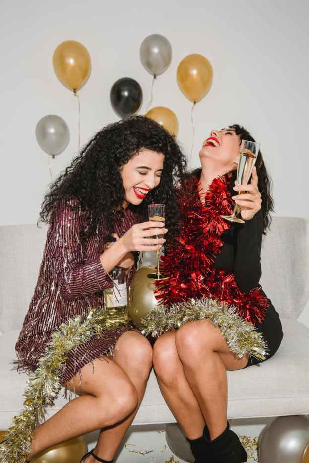 happy women with champagne and tinsel laughing near balloons