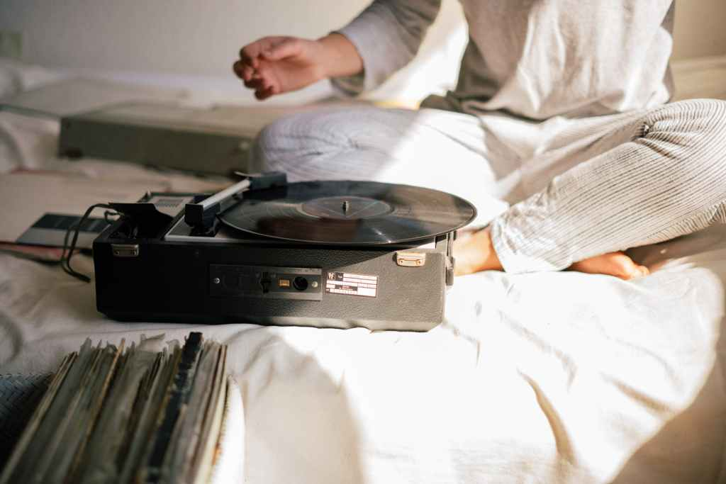 person in white long sleeve shirt in front of vinyl record