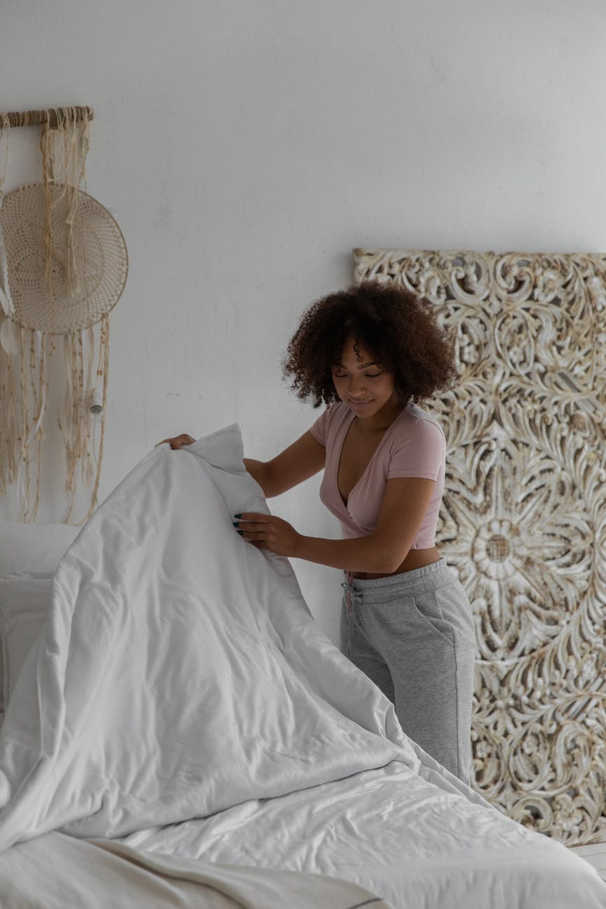 young black lady making bed in sunny morning