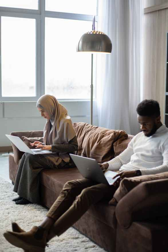 multiethnic couple of freelancers working on laptops on sofa at home