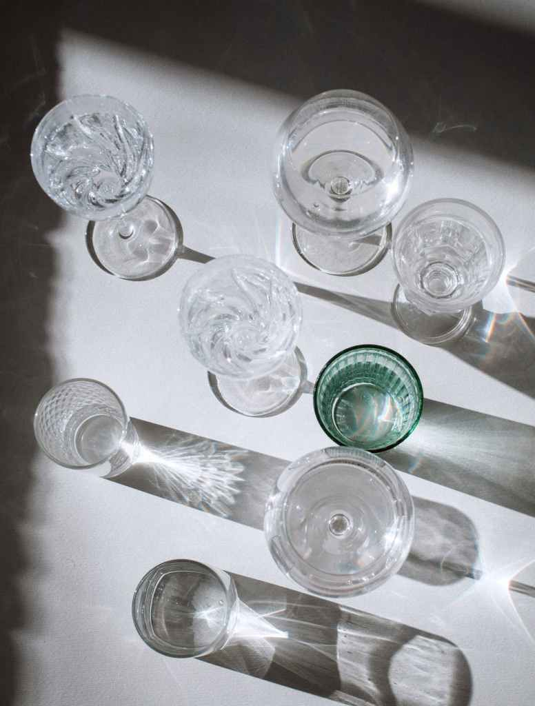 assorted glasses on shiny surface with shadows in sunlight