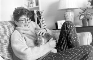 black and white image of Ellie - a non-binary person with short curly hair cuddling a bunny.