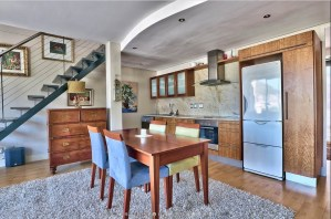Open plan apartment kitchen with stone backsplash and veneer cupboards