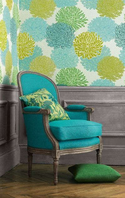 Vintage chair upholstered in bright turquoise fabric against the backdrop of grey wainscoting and contemporary wallpaper