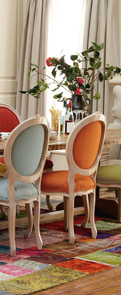 Dining room with the antique style chairs upholstered in different coloured fabrics.