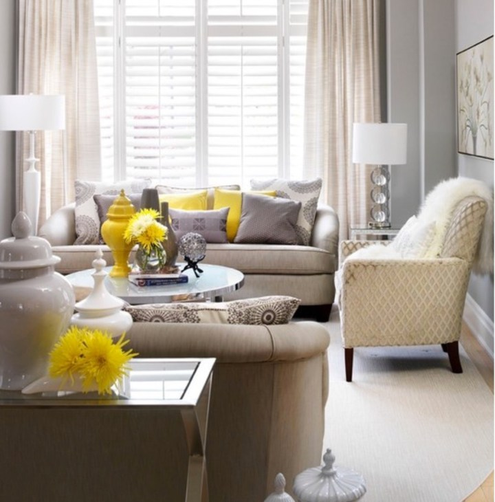 Small living room with small sofa and yellow and pale grey throw cushions and walls