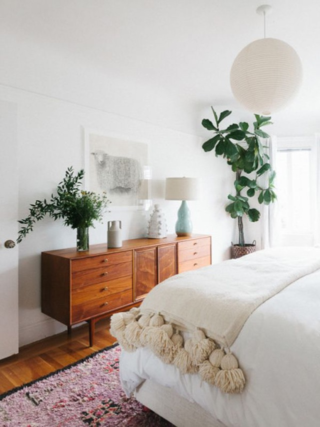 bedroom with vintage credenza and plants