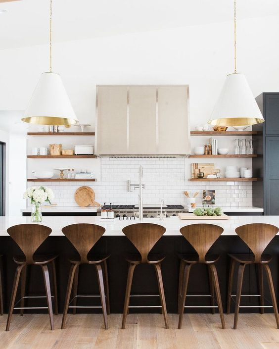 Kitchen remodel with large white and gold pendants open timber shelves and stained wood chairs