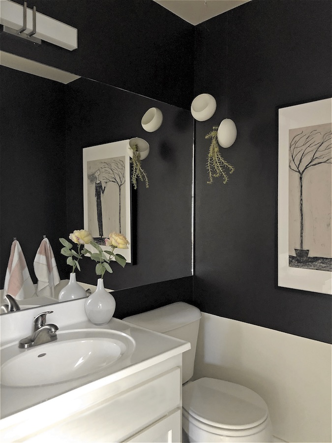 Powder room upgrade with dark walls and large mirror