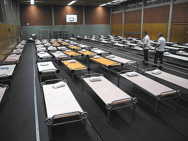 DRK-Einsatzleiter Steffen Schmidt (links) inspiziert die Betten für die Flüchtlinge in der Halle im Bergisch Gladbacher Ortsteil Sand