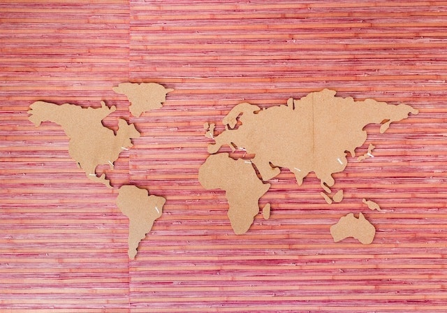 Cardboard cutouts of world map on pink background