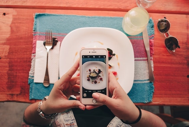 Person taking a photo of a meal with their mobile phone