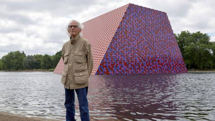 Bulgarian artist Christo Vladimirov poses with photographers next to his work 'La Mastaba' on London's Serpentine Lake in 2018 (NIKLAS HALLE'N / AFP)