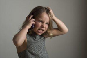 電話が繋がらないので怒る少女