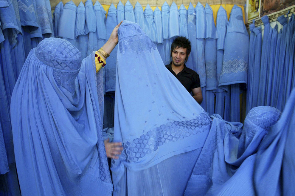 An Afghan woman checks out a Burqa at a Burqa Shop in Herat