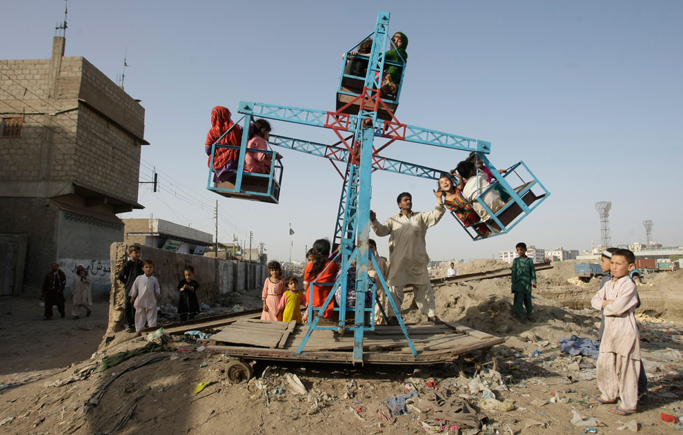 Pakistani children enjoy swings in the slums of Karachi, Pakistan on March 14. (Fareed Khan/Associated Press) #