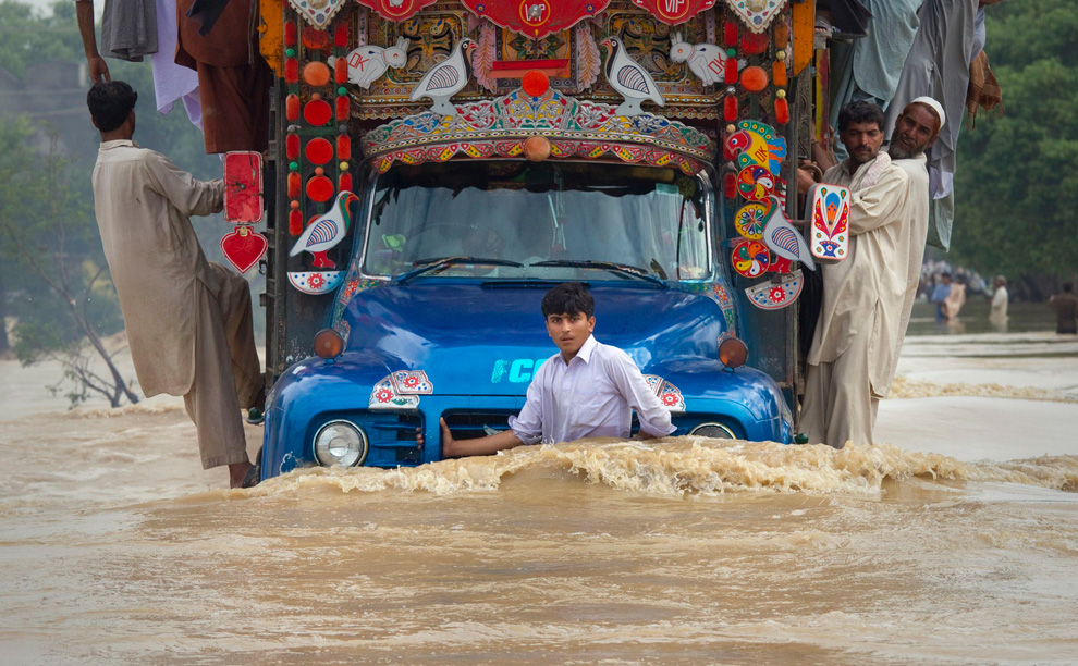 A boy hangs on to the front of a cargo truck while passing through a flooded road in Risalpur, located in Nowshera District in Pakistan's Northwest Frontier Province July 30, 2010. (REUTERS/Adrees Latif)