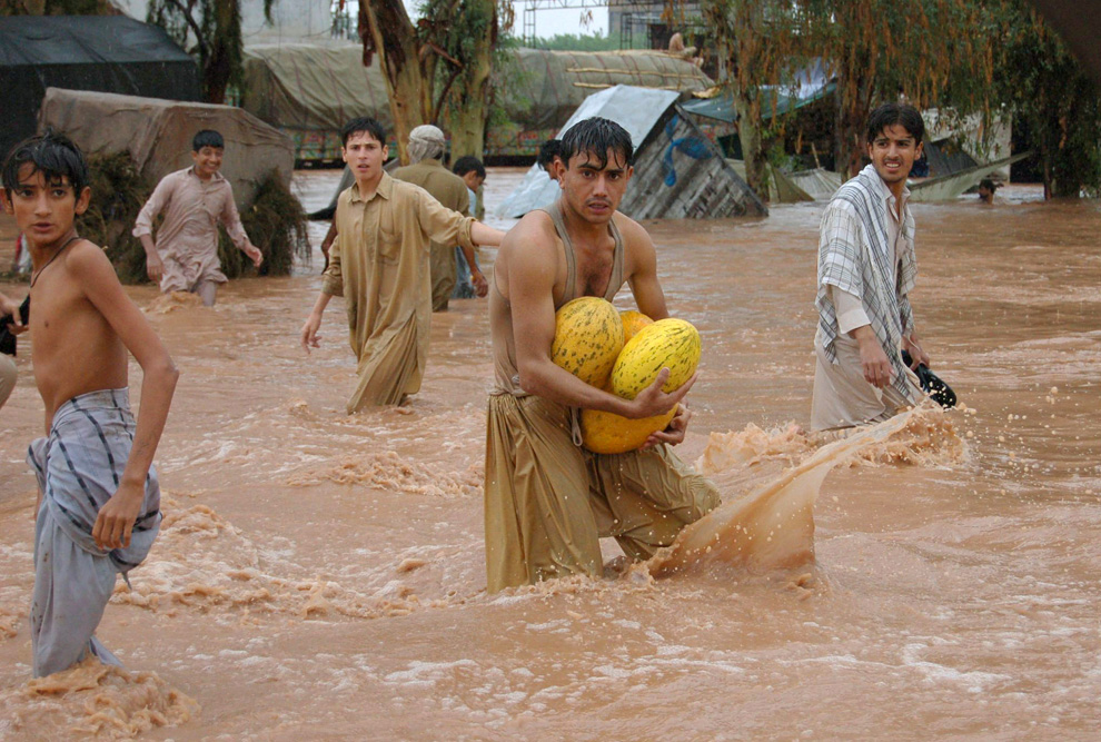 Evacuees wade through a flooded area following heavy monsoon rains in Peshawar on Saturday, July 31, 2010. (AP Photo/Xinhua, Saeed Ahmad)
